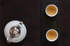 Mjölkar den asiatiska teservisen för vitt porslin med grönt te Oolong på det svarta stenskrivbordet Slut upp, bästa sikt royaltyfri bild