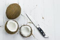 Mjölkar den skräp- nya tropiska bruna vita organiska kokosnöten för kokosnöten kniven på trävit bakgrund Royaltyfria Bilder