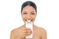 Mjölkar hållande exponeringsglas för den gladlynta svarta haired modellen av Royaltyfri Bild