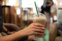 Mjölkar hållande plast- exponeringsglas för kvinnan av med is kaffe med arkivfoton