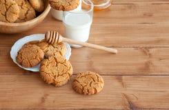 Mjölkar ljust rödbrun kakor för honung med på en lantlig bakgrund royaltyfria bilder