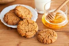 Mjölkar ljust rödbrun kakor för honung med på en lantlig bakgrund arkivfoto