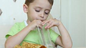 Mjölkar lyckliga drinkar för ett barn till och med ett sugrör och matningar på dillanderör som sitter på en tabell Rörelse av kam arkivfilmer