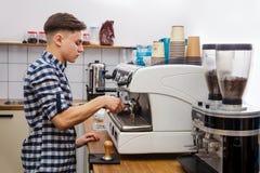 Mjölkar varm ånga för unga stiliga för baristahipsterdanande för kaffe för kafét för mannen korn för maskinen cappuccino för latt royaltyfria foton