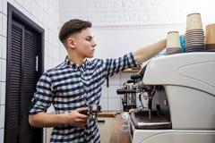 Mjölkar varm ånga för unga stiliga för baristahipsterdanande för kaffe för kafét för mannen korn för maskinen cappuccino för latt arkivfoton