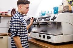 Mjölkar varm ånga för unga stiliga för baristahipsterdanande för kaffe för kafét för mannen korn för maskinen cappuccino för latt royaltyfri foto
