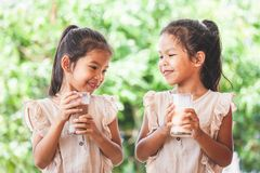 Mj?lkar dricka f?r tv? gulligt asiatiskt barnflickor fr?n exponeringsglas tillsammans royaltyfria bilder