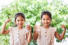 Mj?lkar dricka f?r tv? gulligt asiatiskt barnflickor fr?n exponeringsglas tillsammans royaltyfria foton
