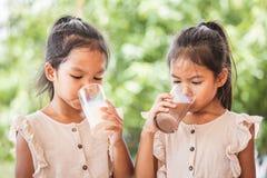 Mj?lkar dricka f?r tv? gulligt asiatiskt barnflickor fr?n exponeringsglas tillsammans fotografering för bildbyråer