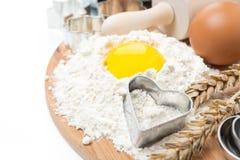 Mjöl, ägg, kavel och bakningformer på träbräde Arkivbild