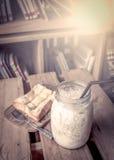 Mjölka med rostat bröd på trätabellen med böcker Arkivbilder