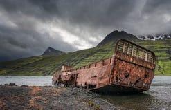 Mjoifjordur,冰岛-被放弃的渔船在海湾生锈 免版税库存图片