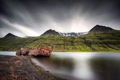 Mjoifjordur,冰岛-被放弃的渔船在海湾生锈 免版税图库摄影
