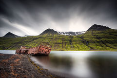 Mjoifjordur, Исландия - покинутая рыбацкая лодка ржавеет в фьорде Стоковая Фотография RF