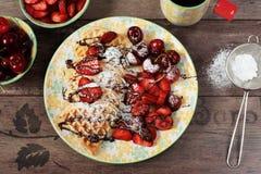 Mjuk belgisk hjärta formade dillandear med körsbär och jordgubbar, chokladtoppning och pudrat socker på den gula plattan Svart te fotografering för bildbyråer