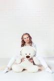 Mjuk blond flicka som kramar nallebjörnen Royaltyfri Foto