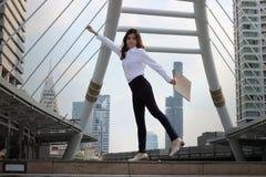 Mjuk fokus av den lyckade unga asiatiska affärskvinnan som lyfter hennes armar med dokumentmappen på stads- byggnadsbakgrund arkivbilder