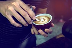 Mjuk fokus på Barista som utför expertis av hällande lattekonst i vingtulpanmodell, genom att använda den handleless kannan Selek arkivfoton