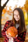 Mjuk fokusstående av en ung flicka med en pumpa Arkivbild