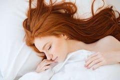Mjuk kvinna med rött hår som sover i säng arkivfoto
