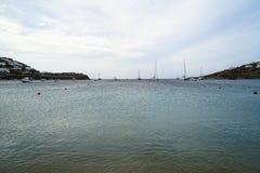 Mjuk scenisk härlig seascape med segelbåtar, yachter, klar himmel-, berg- och vitbyggnadsbakgrund, Ornos strand royaltyfri fotografi