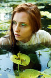 Mjuk simning för ung kvinna i dammet bland näckrors Fotografering för Bildbyråer