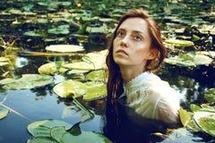Mjuk simning för ung kvinna i dammet bland näckrors Royaltyfri Fotografi