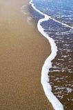 Mjuk våg av det blåa havet på den sandiga stranden Bakgrund Arkivfoto