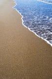 Mjuk våg av det blåa havet på den sandiga stranden Bakgrund Arkivfoton