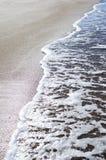 Mjuk våg av det blåa havet på den sandiga stranden Bakgrund Arkivbilder
