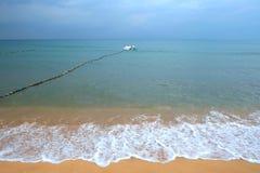 Mjuk våg av havet på den sandiga stranden Fartyget är i bakgrunden Royaltyfria Bilder