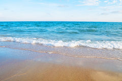 Mjuk våg på den sandiga stranden av det tropiska havet royaltyfri foto