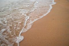 Mjuk våg på stranden på aftonen Arkivbild