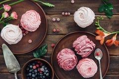 Mjuk vaniljmarängefterrätt med vita blommor, träbackgro Fotografering för Bildbyråer
