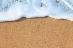 Mjuk våg av havet på den sandiga stranden - bakgrund Arkivbilder
