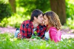 Mjuka par som är förälskade i vårträdgård Arkivfoto