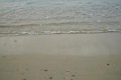 Mjuka sand och små vaggar stranden med havsvatten och vit skummande vågbakgrund och copyspace på den Ornos kusten arkivbild