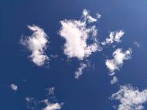 Mjuka vita moln av utsmyckad form mot blå himmel arkivbild