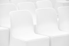 Mjuka vita stolar står i rad Arkivfoto