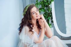 Mjukhet- och sensualitetbegrepp Härlig brunettmodell som poserar på säng i vit damunderkläder Sinnlig stående av barn royaltyfria bilder