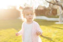 Mjukt fokusfoto av den lilla lockiga flickan med två svansar som går i trädgården på det gröna gräset Royaltyfri Foto