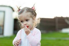 Mjukt fokusfoto av den lilla lockiga flickan med två svansar som går i trädgården på det gröna gräset Royaltyfria Bilder