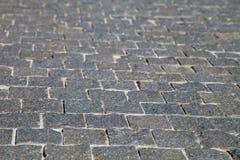 Mjukt fokusslut upp grå backgrou för textur för kullerstenvägslinga Royaltyfria Foton