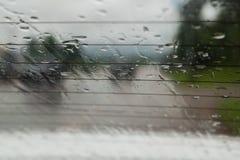 Mjukt skott av droppar av regn på bilexponeringsglasbakgrund arkivfoton