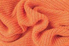 Mjukt stuckit tyg från orange fluffigt garn royaltyfria bilder