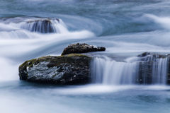 Mjukt vatten över stenar i blå flodström Fotografering för Bildbyråer