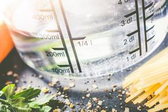 250 ml - ccm Water In A Measuring Cup Surrounded By Noodles, Herbs And Spices stock photo