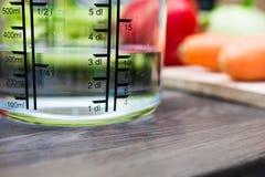 300ml/3dl da água no copo de medição de A em um contador de cozinha com vegetais Fotos de Stock Royalty Free