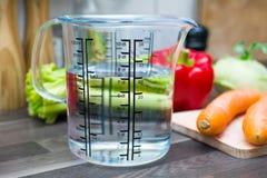700ml/7dl des Wassers in einem Messbecher auf einer Küchenarbeitsplatte mit Gemüse Stockfotografie