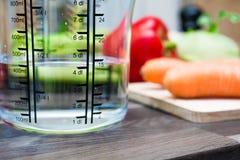 400ml/4dl des Wassers in einem Messbecher auf einer Küchenarbeitsplatte mit Gemüse Stockfoto